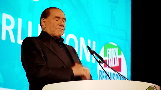 Silvio Berlusconi at the lectern speaking at an event in Milan Italy