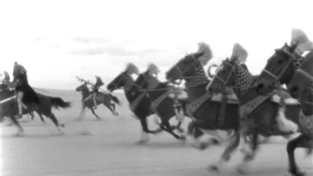 vídeos y material grabado en eventos de stock de dx - similar to: rome - cloud-filled sky - c.s. - travel as roman two-horse chariots race r to l across desert - horsemen with spears riding b.g. - then pan away l past horsemen - b&w. - soldado romano