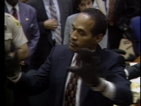 oj simpson is asked to try on the bloody glove in front of the jury and his hand is unable to slide completely in the glove - handschuh stock-videos und b-roll-filmmaterial