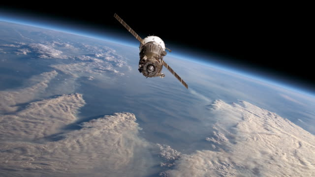 simulation of space satellite above thick clouds of earth's atmosphere - telekommunikationsgerät stock-videos und b-roll-filmmaterial