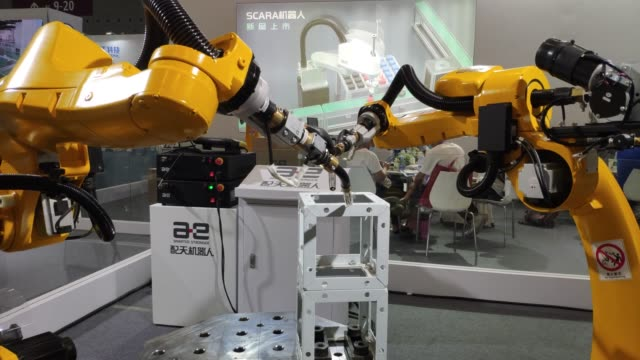 vídeos de stock e filmes b-roll de simultaneous weldings robots are on display at the stand of peitian robotics during the 2020 shenzhen international industrial manufacturing... - coordenação