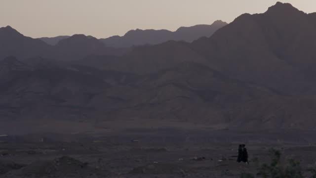 w/s sinai desert near dahab, group of arab men crossing the frame, mountains in background - sinai egitto video stock e b–roll