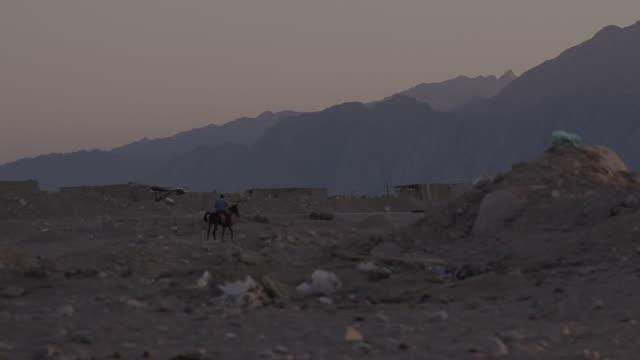 W/S Sinai desert near Dahab, rider and horse walking between rubbish, mountains background