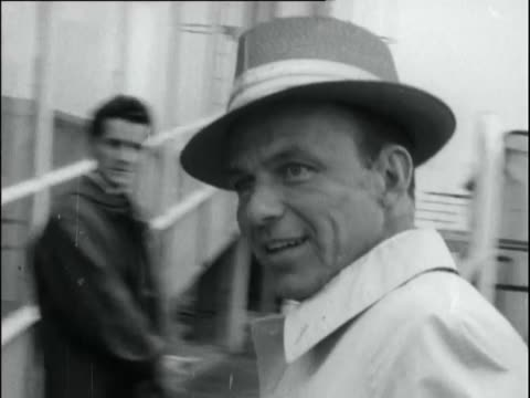 sinatra walks down stairway from plane onto tarmac carrying his bags, smiles briefly into camera. - frank sinatra stock videos & royalty-free footage