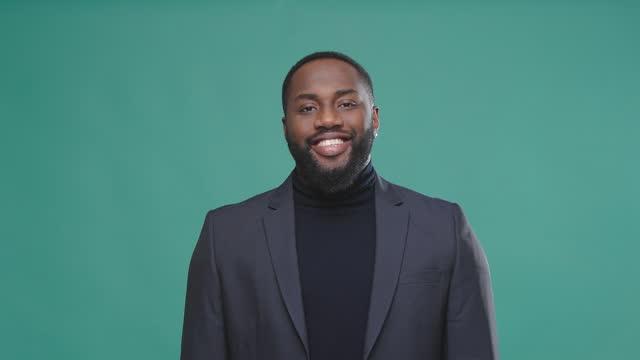 vídeos de stock e filmes b-roll de sincere afro american man in jacket smiles on green background - afro americano