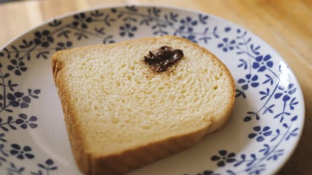 vídeos de stock, filmes e b-roll de cantar chocolate espalhado e banana fatiada no pão brioche fazendo uma cara no café da manhã - lanche