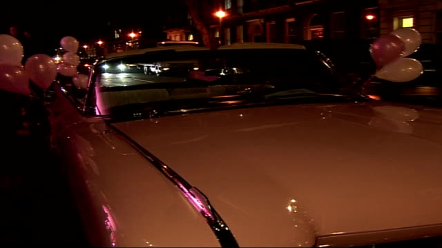 vídeos de stock, filmes e b-roll de singalong dvd of musical 'grease' launch at allstar lanes ext vintage pink cadillac decorated with pink balloons parked on street backdrop with... - cadillac