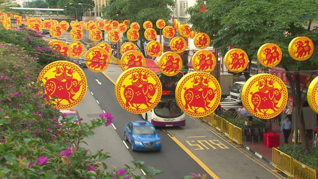 stockvideo's en b-roll-footage met singapore china town close up street decorations red and yellow chinese zodiac symbols zigzaging across the street below with traffic flowing /... - extreme close up