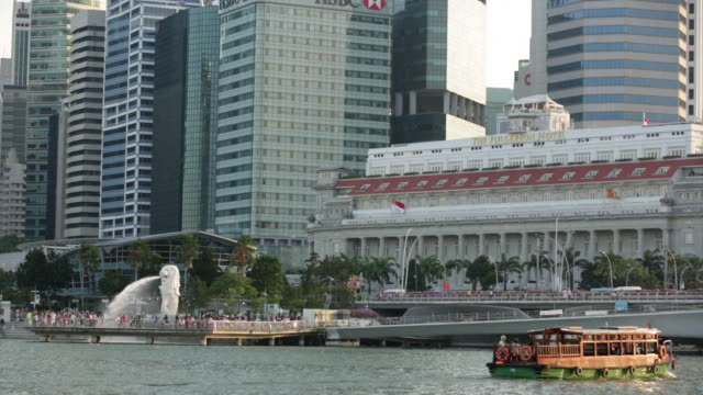 ws singapore cityscape with merlion fountain in foreground. - merlion fictional character stock videos and b-roll footage