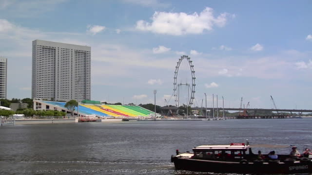 ws, singapore flyer at marina bay, tour boats in foreground, singapore - singapore flyer stock videos and b-roll footage