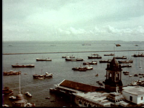 1957 MONTAGE Singapore harbor w/ ships, tankers, freighters + fishing boats. City buildings + parks / Singapore / AUDIO