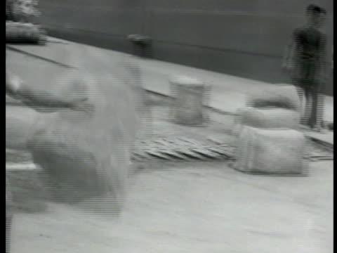 singapore native carrying crude rubber bale on shoulder shipping port bg. rubber bale bouncing across dock worker stacks of rubber bales. cargo net... - 1942 bildbanksvideor och videomaterial från bakom kulisserna
