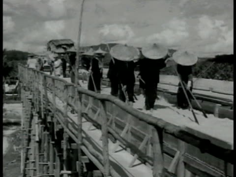 singapore natives in straw hats washing ore in irrigation bridge. workers w/ rakes going through irrigation stream. ship docked in port smoking... - 1942点の映像素材/bロール