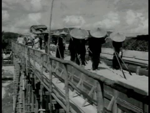 singapore natives in straw hats washing ore in irrigation bridge. workers w/ rakes going through irrigation stream. ship docked in port smoking... - 1942 bildbanksvideor och videomaterial från bakom kulisserna