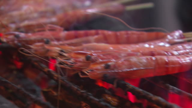 stockvideo's en b-roll-footage met singapore night food market close up of prawns/shrimp on sticks cooking over glowing red hot coals / prawns/shrimp being marinated by cook / wider... - steurgarnaal