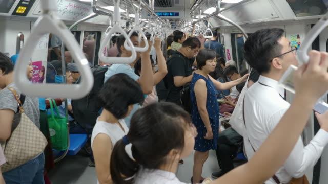 singapore, singapore - november 5 2018: commuters ride inside a speeding mrt subway train - bahnreisender stock-videos und b-roll-filmmaterial