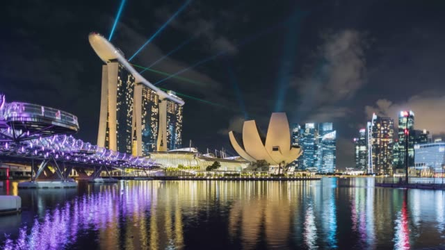 vidéos et rushes de singapore skyline during evening light show, showing helix bridge and marina bay - singapour