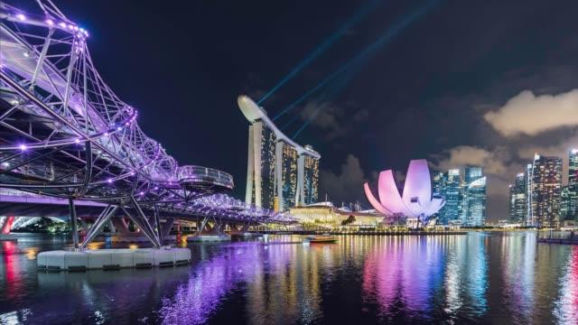 singapore skyline during evening light show, showing helix bridge and marina bay - helix bridge stock videos & royalty-free footage
