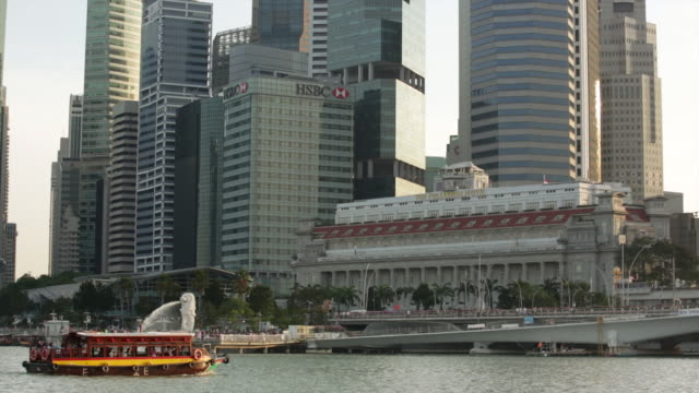 ws singapore skyline with boat passing by merlion fountain. - animal representation stock videos & royalty-free footage