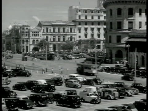 vidéos et rushes de singapore street w/ cars buses buildings parking lot. traffic officer directing w/ hand signals wearing sign on back. vs cattle carts rickshaws cars... - 1942