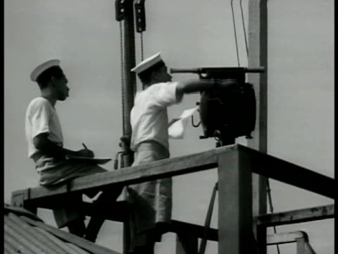 vidéos et rushes de singaporean sailors manning signal light tower. busy harbor large & small boats fishing boats barbed wires fg. sailors w/ large packs boarding ship... - 1942