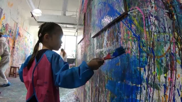 singaporeans dressed in overalls squirt paint onto walls and canvases using water pistols and syringes at a new popup art studio where people get... - squirting stock videos and b-roll footage