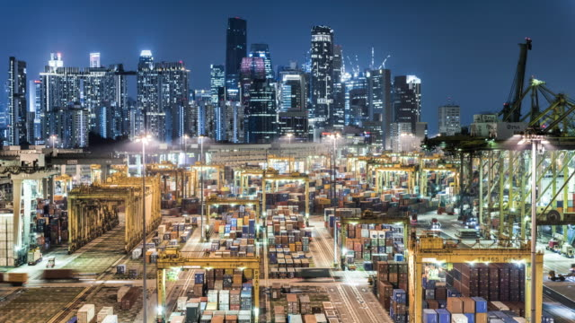 vidéos et rushes de t/l of singapore's cargo container port at night infront of skyline and financial district - container