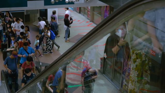 singapore,singapore - november 6 2018: commuters moving through the walkway on the subway (mrt) underground system - republik singapur stock-videos und b-roll-filmmaterial