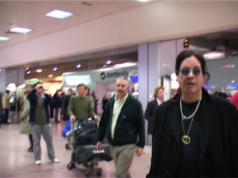 singer and reality tv star ozzy osbourne walks through public area at heathrow after arriving on a flight from la ready for concert appearances - reality fernsehen stock-videos und b-roll-filmmaterial