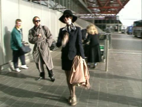 singer celine dion flies out through heathrow airport. carries coat and walks alongside london bus before walking into terminal. - シンガーソングライター点の映像素材/bロール