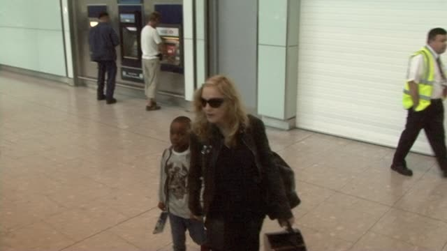 vídeos y material grabado en eventos de stock de singer madonna arrives at heathrow and walks hand in hand with her adopted son david he turns round and looks inquisitively at media - adopción