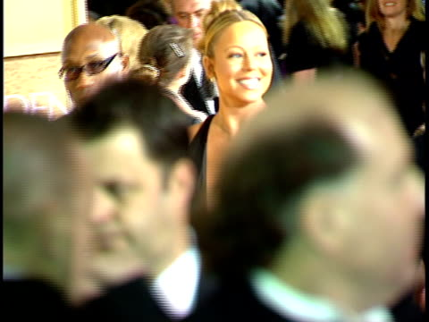 Singer Mariah Carey walking w/ group through crowded red carpet at Beverly Hilton hotel some heads FG