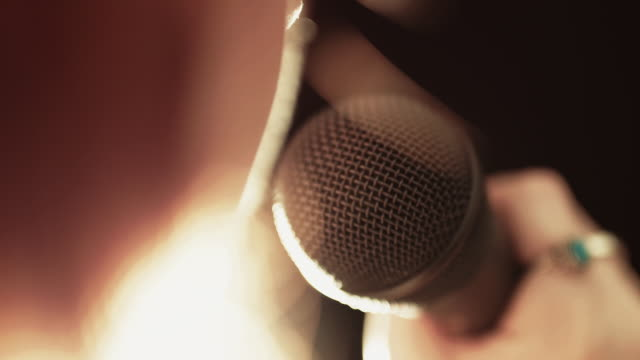 singer raising microphone to mouth & singing - microphone stock videos & royalty-free footage