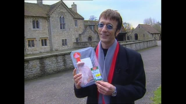 singer robin gibb at his home in oxfordshire, united kingdom, presented with packet of lamb and joking he will sell it on the black market as he is... - portionspåse bildbanksvideor och videomaterial från bakom kulisserna