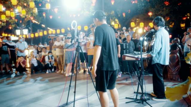 vidéos et rushes de singer singing in street at night - vie citadine