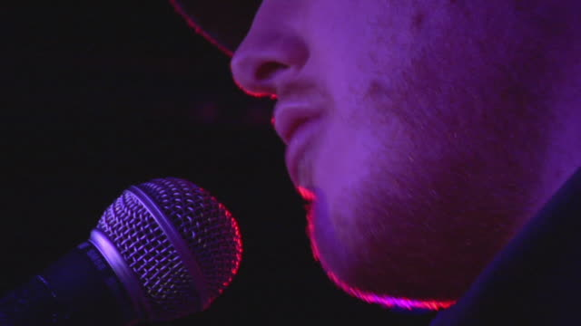 ecu zo cu singer singing to microphone on stage, london, england, uk - cantante video stock e b–roll