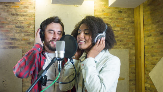 Singers singing at a recording studio