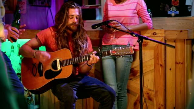 vídeos de stock e filmes b-roll de cantor/compositor a tocar na barra de local - bar local de entretenimento