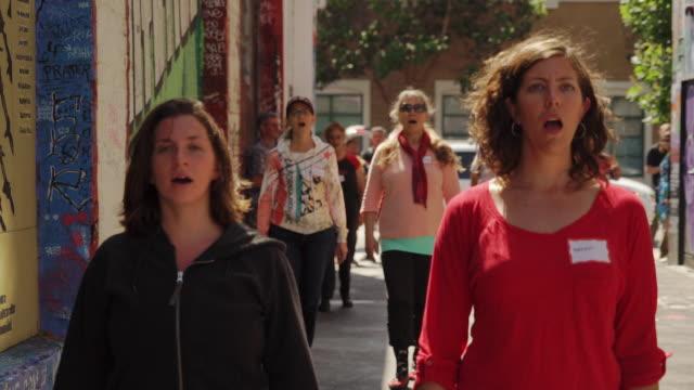 singing and walking women near street art (graffiti) in clarion alley, san francisco, usa - cerimonia video stock e b–roll