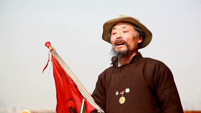 singing Chinese old man with a medal