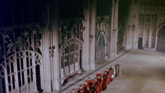 1957 MONTAGE Singing choirboys in line follow a priest into church / United Kingdom