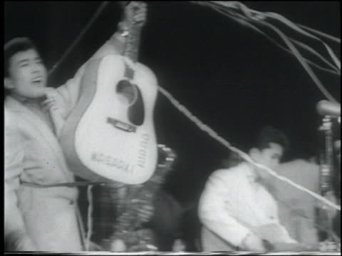 vídeos de stock, filmes e b-roll de b/w 1958 newsreel pan singing guitarist in rockabilly band on stage in concert / tokyo - 1958