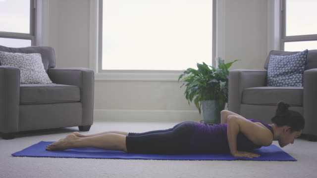 自宅でヨガを行う単一の大人の女性 - 胡坐点の映像素材/bロール
