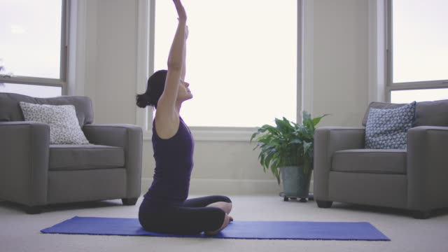 single adult female doing yoga at home - fatcamera stock videos & royalty-free footage