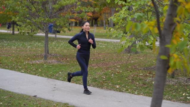 Single adult female jogging through a park during Autumn