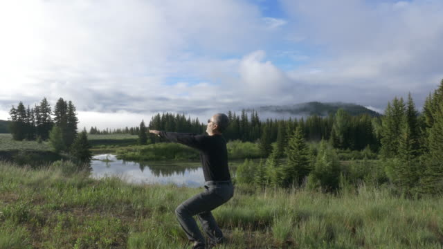 vídeos de stock, filmes e b-roll de single asian man exercising near a pond in the morning with snowcapped mountain view in the background - prendendo a respiração