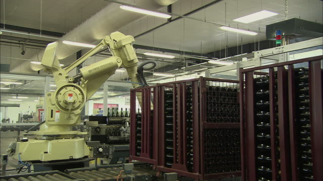 ms single assembly line robot moves stacks of bottles from storage bins on top conveyor belt in factory / reims, champagne, france - bottling plant stock videos & royalty-free footage