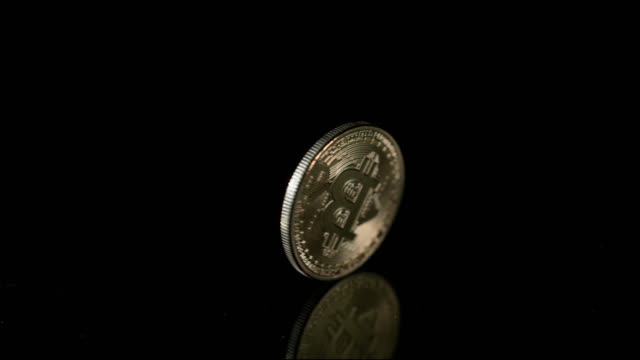 a single bitcoin spins in slow motion on a reflective black surface - bitcoin stock videos and b-roll footage