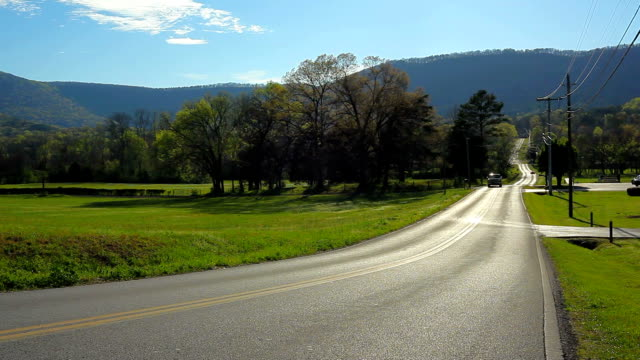 single car driving on sunny country road with mountain in background - 散歩道点の映像素材/bロール