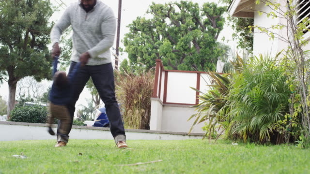 single dad and son playing outside in the yard - single father stock-videos und b-roll-filmmaterial